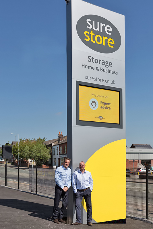 Sure store management pictured beside new signage